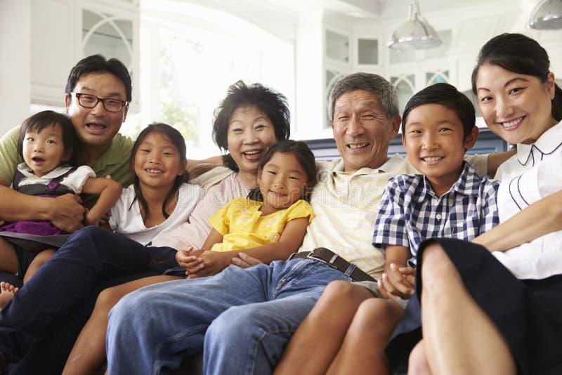 Retrato del grupo de la familia extensa que se sienta en casa en el sofá imagenes de archivo