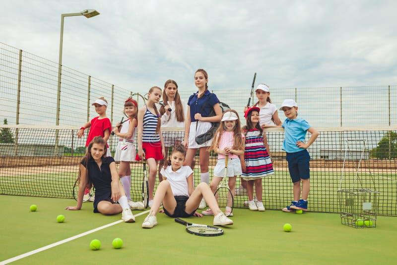 Retrato del grupo de muchachas como jugadores de tenis que celebran la estafa de tenis contra hierba verde de la corte al aire li fotos de archivo