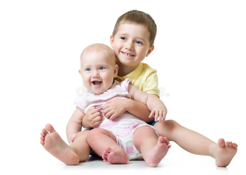 Retrato del hermano que abraza a su pequeña hermana linda que se sienta en el piso aislado en el fondo blanco foto de archivo
