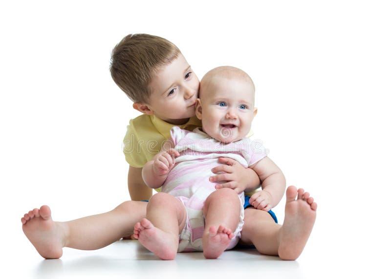 Retrato del hermano que besa a su pequeña hermana linda que se sienta en el piso aislado en el fondo blanco foto de archivo libre de regalías