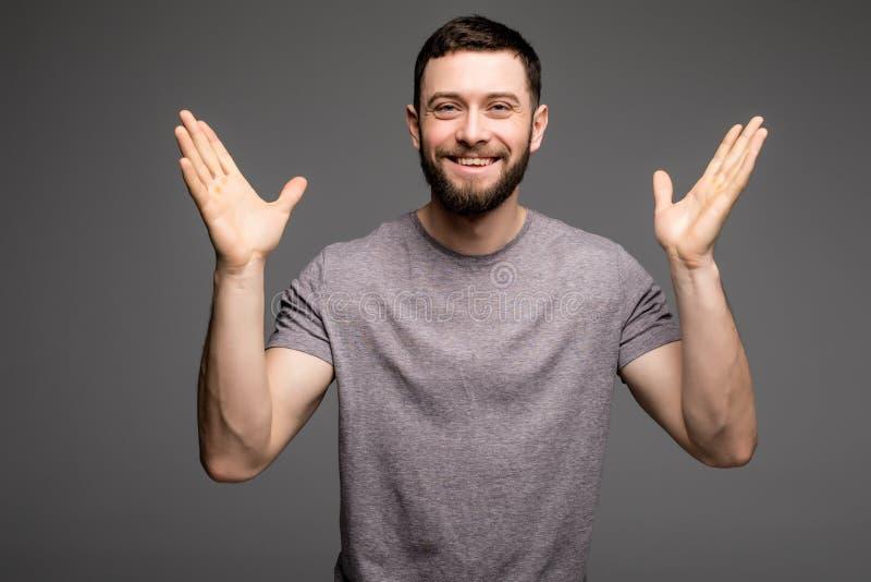 Retrato del hombre acertado feliz con las manos aumentadas imagen de archivo libre de regalías