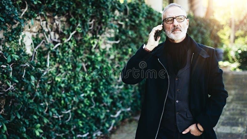 Retrato del hombre adulto atractivo que habla en su smartphone mientras que camina en parque de la ciudad Fondo horizontal, borro foto de archivo