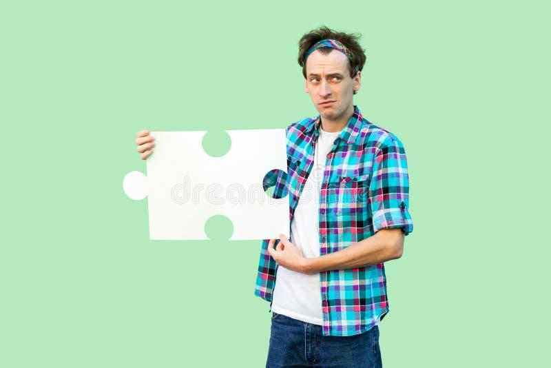 Retrato del hombre adulto joven de la tristeza en la camisa a cuadros que coloca y que lleva a cabo el pedazo grande de rompecabe foto de archivo