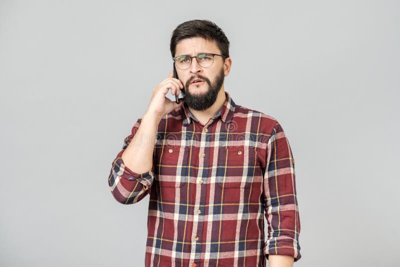Retrato del hombre adulto ocupado que habla en el teléfono, expresando seriedad imágenes de archivo libres de regalías