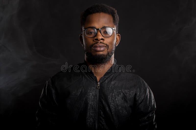 Retrato del hombre africano joven hermoso en fondo negro imagen de archivo libre de regalías