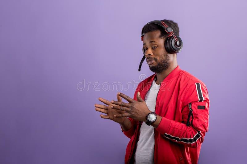 Retrato del hombre africano joven que escucha la m?sica con los auriculares fotografía de archivo