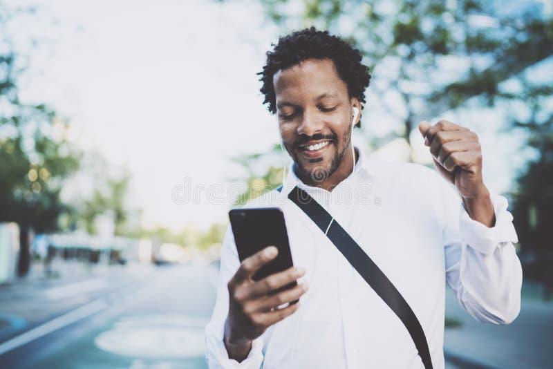 Retrato del hombre afroamericano sonriente en standidng de los auriculares en calle soleada que goza a la música en su teléfono e foto de archivo
