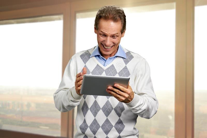 Retrato del hombre alegre que habla usando la tableta foto de archivo
