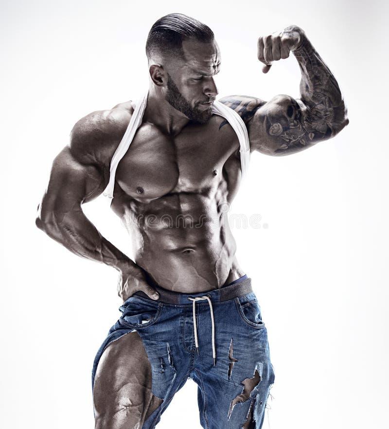 Retrato del hombre atlético fuerte de la aptitud que muestra los músculos grandes foto de archivo libre de regalías