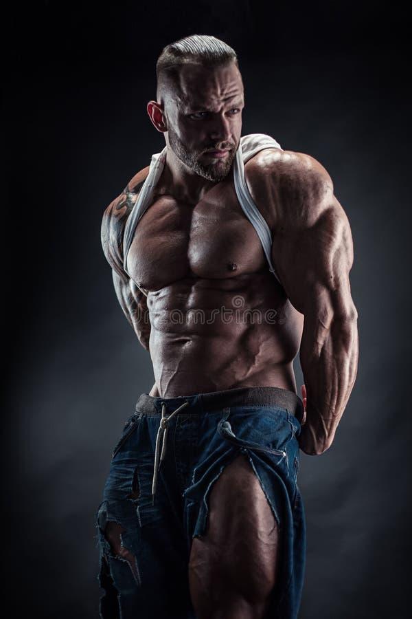 Retrato del hombre atlético fuerte de la aptitud que muestra los músculos grandes foto de archivo
