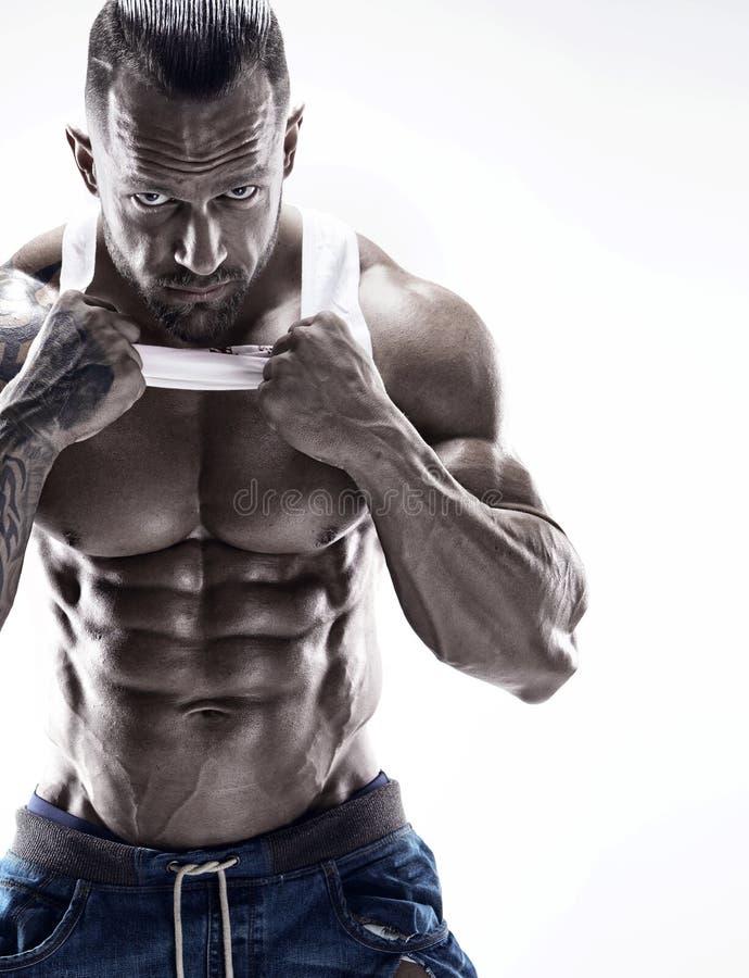 Retrato del hombre atlético fuerte de la aptitud que muestra los músculos grandes imagenes de archivo