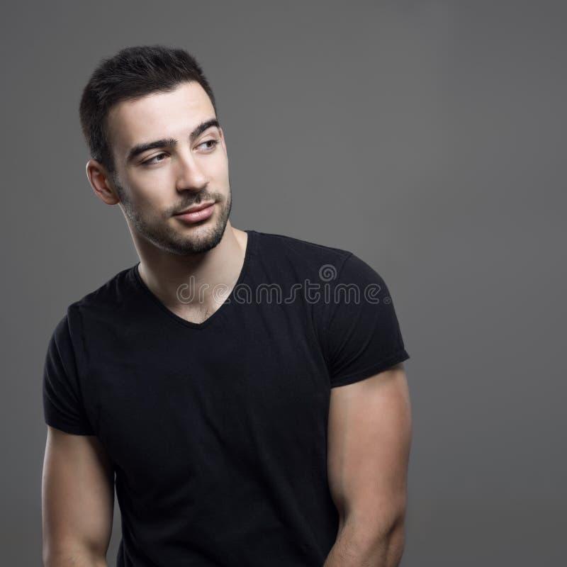 Retrato del hombre atlético joven en la camisa negra que mira lejos sobre hombro imagen de archivo