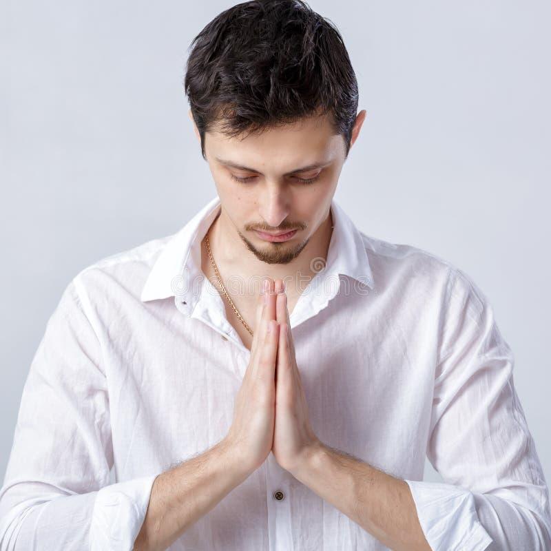 Retrato del hombre atractivo con el pelo oscuro en la camisa blanca en yoga imagenes de archivo