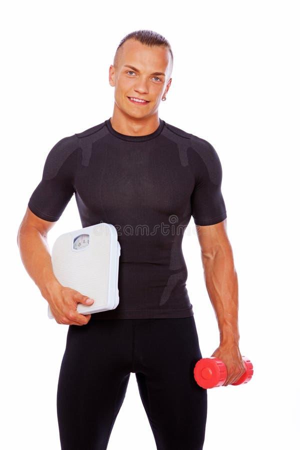 Retrato del hombre atractivo con pesas de gimnasia y escalas imagen de archivo libre de regalías