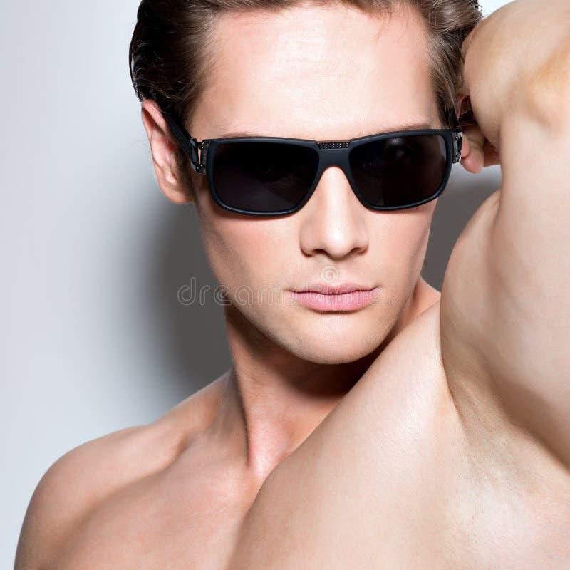 Retrato del hombre atractivo muscular joven en vidrios foto de archivo