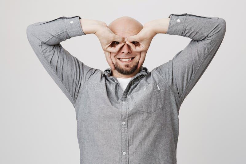 Retrato del hombre barbudo divertido feliz que usa sus manos para mostrar los vidrios que engañan alrededor sobre el fondo blanco foto de archivo
