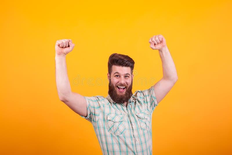Retrato del hombre barbudo feliz con los puños encima del celebratin sobre fondo amarillo imagen de archivo
