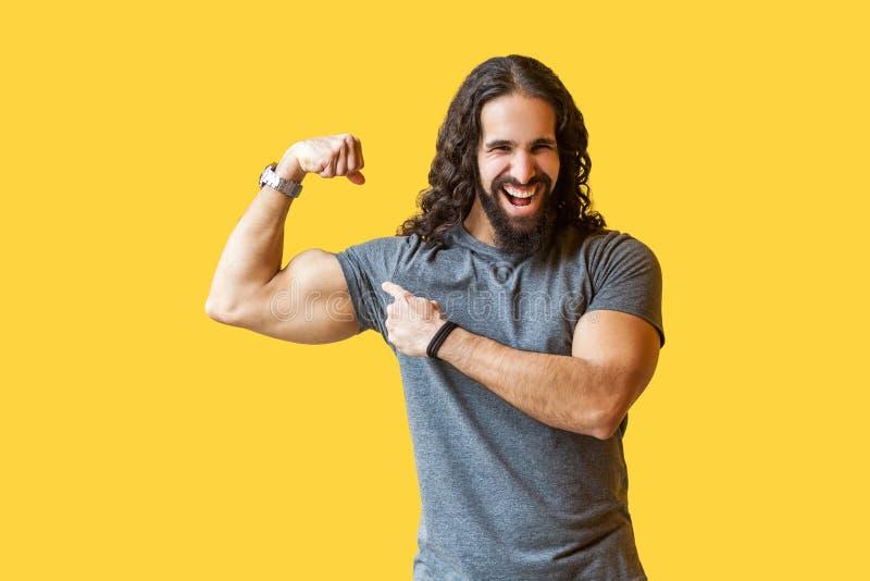 Retrato del hombre barbudo fuerte divertido del culturista con el pelo rizado largo en la situación gris de la camiseta, señaland imágenes de archivo libres de regalías