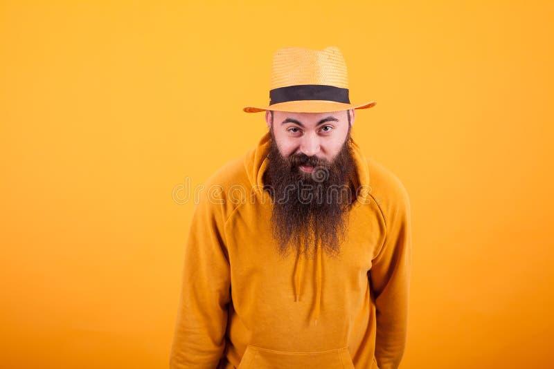Retrato del hombre barbudo hermoso con el sombrero anaranjado que mira intrigado la cámara sobre fondo amarillo foto de archivo libre de regalías