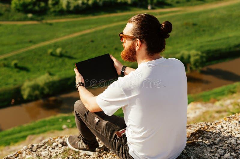 Retrato del hombre barbudo hermoso joven del inconformista que usa una tableta afuera fotografía de archivo