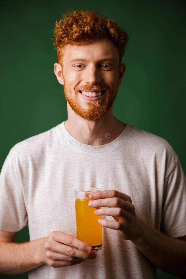 Retrato del hombre barbudo hermoso que sostiene el vidrio de zumo de naranja fotos de archivo