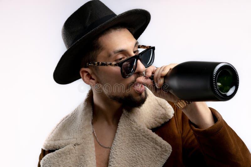 Retrato del hombre barbudo joven en sombrero negro y capa marr?n en lentes de sol negros, bebiendo de una botella negra aislada imagen de archivo