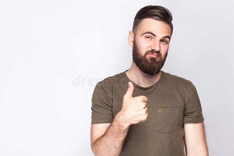 Retrato del hombre barbudo satisfecho con los pulgares para arriba y la camiseta verde oscuro contra fondo gris claro imagenes de archivo