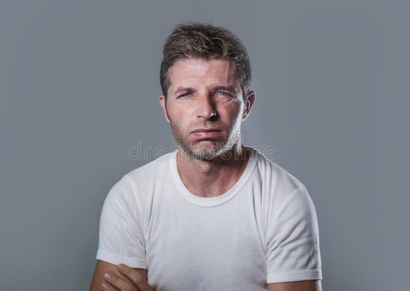 Retrato del hombre caucásico atractivo y subrayado joven en parecer agujereado y cansado blanco de la camiseta decepcionado y ago imagen de archivo