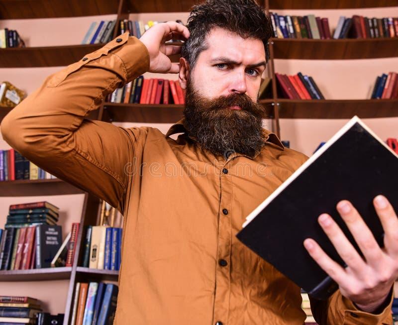 Retrato del hombre con la barba y del buen libro de lectura de los ojos a disposición en fondo del estante Concepto de la educaci imagen de archivo