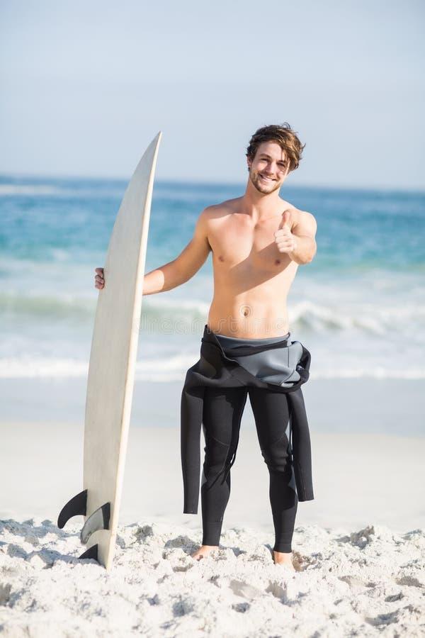 Retrato del hombre con la tabla hawaiana que muestra su pulgar para arriba en la playa imágenes de archivo libres de regalías