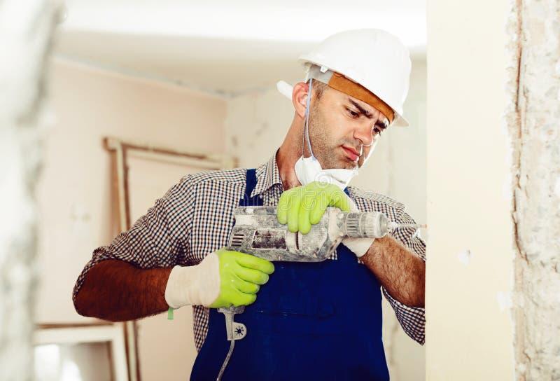 Retrato del hombre concentrado del reparador que se coloca con el taladro interior imagenes de archivo