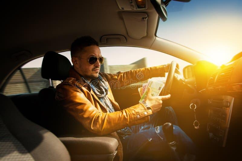 Retrato del hombre concentrado que conduce el coche con mucho maney EUR imagenes de archivo