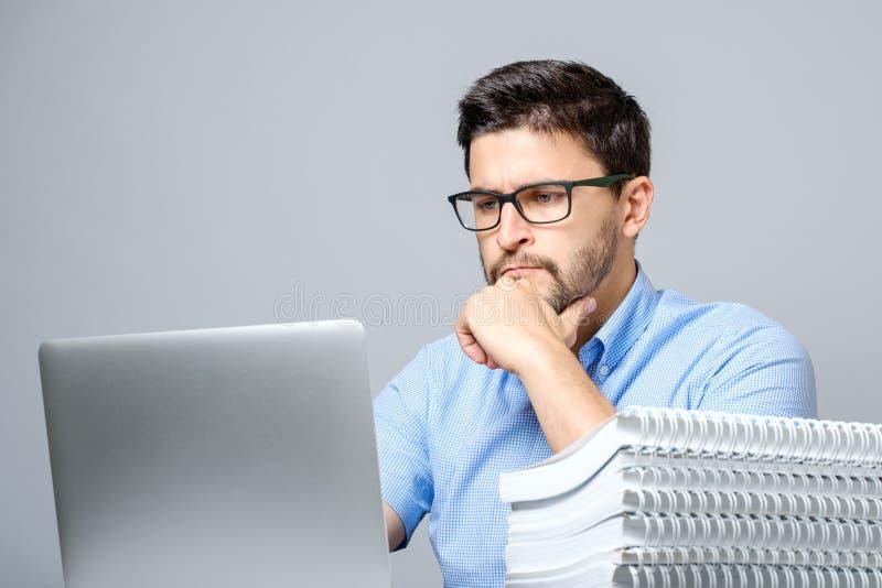 Retrato del hombre concentrado serio que trabaja en el ordenador portátil fotos de archivo