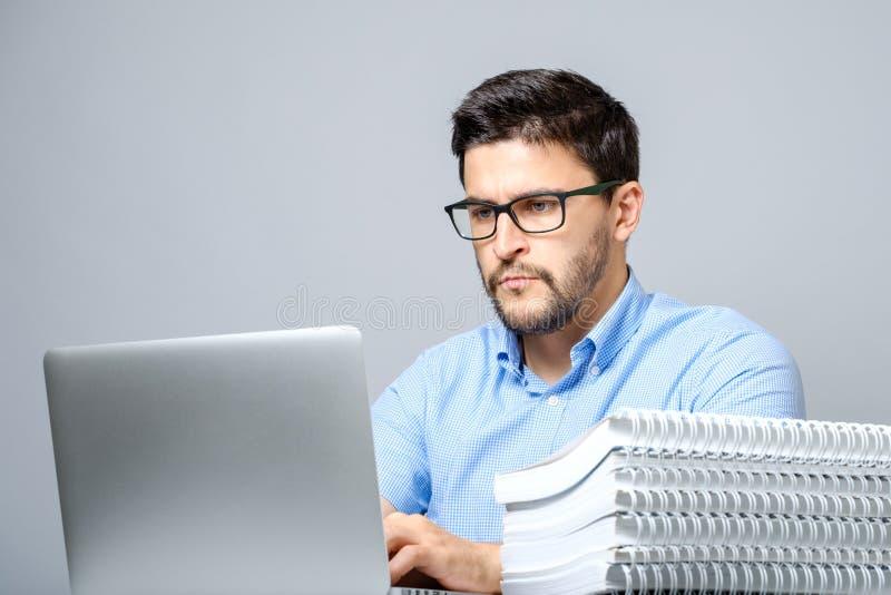 Retrato del hombre concentrado serio que trabaja en el ordenador portátil imágenes de archivo libres de regalías