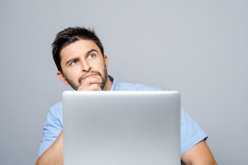 Retrato del hombre concentrado serio que trabaja en el ordenador portátil foto de archivo libre de regalías