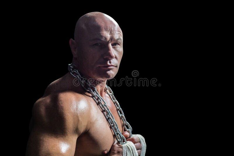 Retrato del hombre confiado del culturista que sostiene la cadena fotografía de archivo libre de regalías