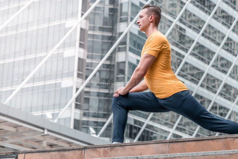 Retrato del hombre del corredor que estira las piernas en la ciudad al aire libre foto de archivo