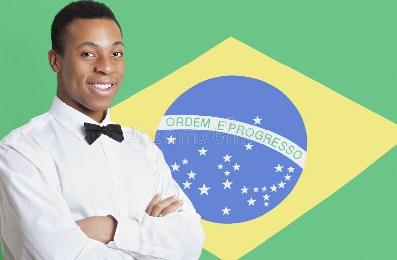 Retrato del hombre de la raza mixta contra bandera brasileña imagen de archivo libre de regalías