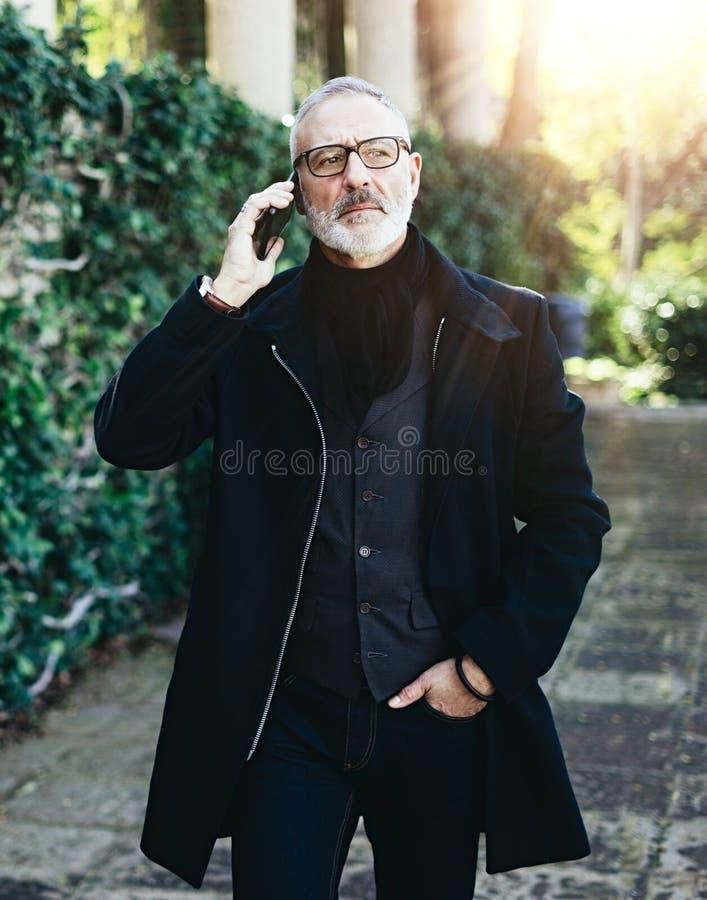 Retrato del hombre de negocios adulto atractivo que habla en su smartphone mientras que camina en parque de la ciudad Vertical, b fotos de archivo libres de regalías