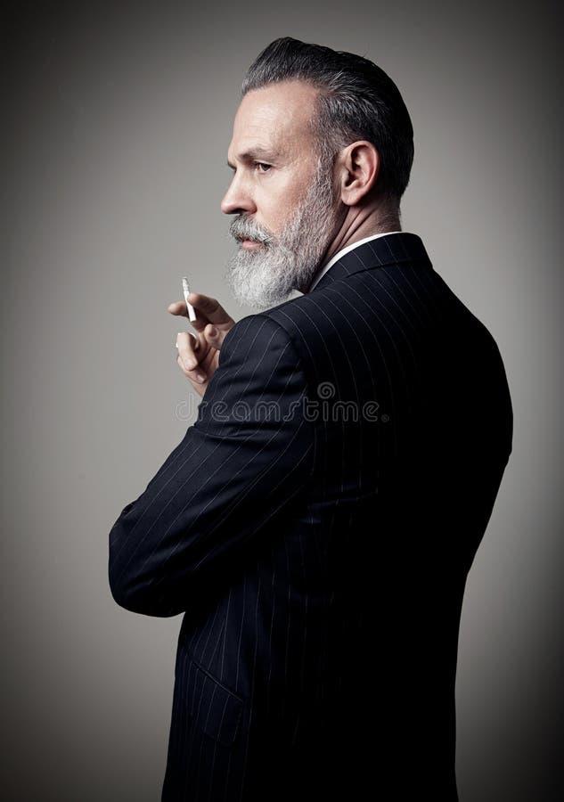 Retrato del hombre de negocios adulto que lleva el traje de moda y que sostiene el cigarrillo contra la pared vacía Maqueta verti fotografía de archivo