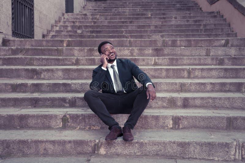 Retrato del hombre de negocios afroamericano hermoso que habla en aire libre que se sienta móvil en las escaleras de la ciudad imágenes de archivo libres de regalías