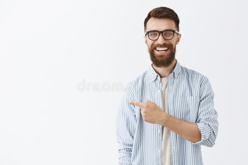 Retrato del hombre de negocios atractivo contento y amistoso alegre con la barba larga en vidrios que señala a la izquierda encan imagenes de archivo