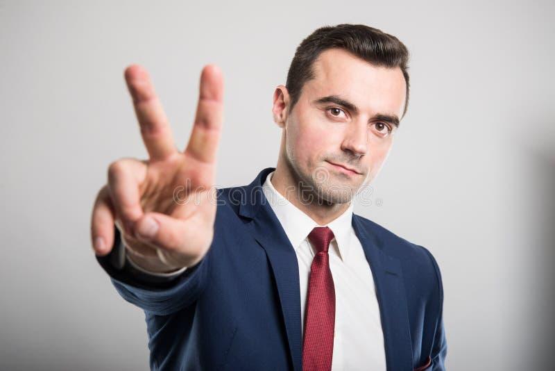 Retrato del hombre de negocios atractivo joven que muestra gesto de la paz fotos de archivo libres de regalías