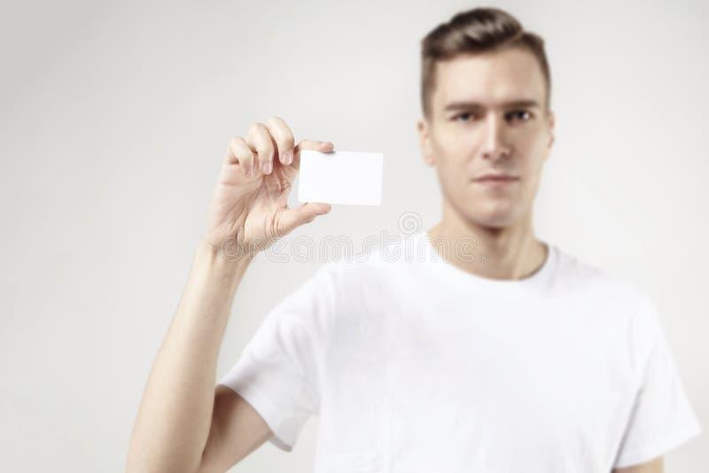 Retrato del hombre de negocios atractivo que sostiene la tarjeta de visita en blanco, espacio vacío para la disposición, con el f imagenes de archivo