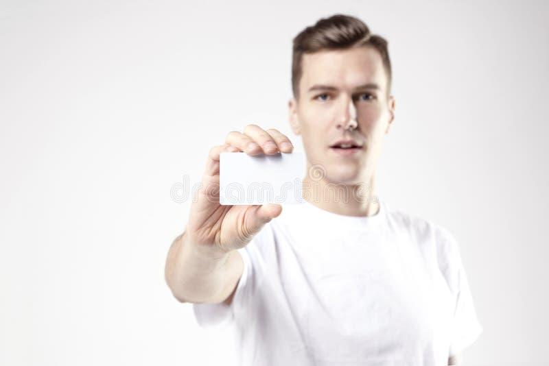 Retrato del hombre de negocios atractivo que sostiene la tarjeta de visita en blanco, espacio vacío para la disposición, con el f imágenes de archivo libres de regalías
