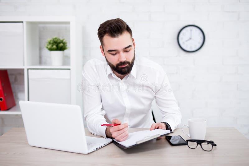 Retrato del hombre de negocios barbudo hermoso que hace papeleo en oficina imagen de archivo