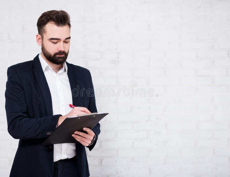 Retrato del hombre de negocios barbudo joven que escribe algo en el tablero sobre el fondo blanco de la pared de ladrillo foto de archivo
