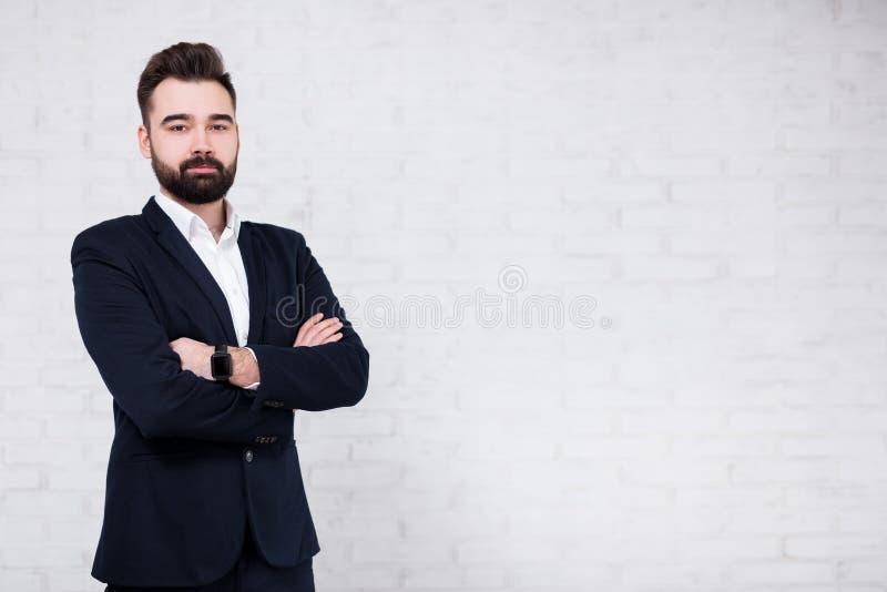 Retrato del hombre de negocios barbudo joven sobre el fondo blanco de la pared de ladrillo foto de archivo