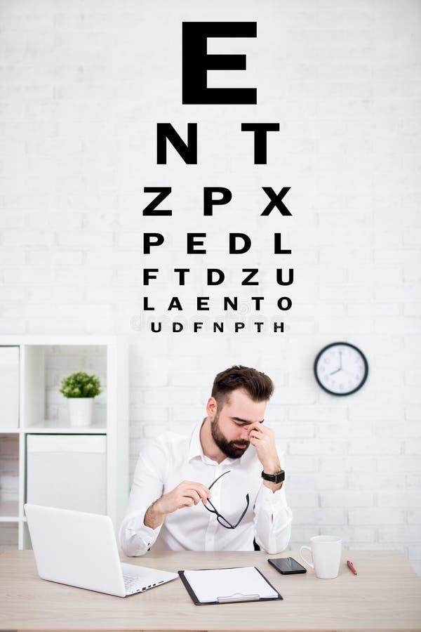 Retrato del hombre de negocios cansado que lleva a cabo las lentes y la carta de prueba del ojo foto de archivo