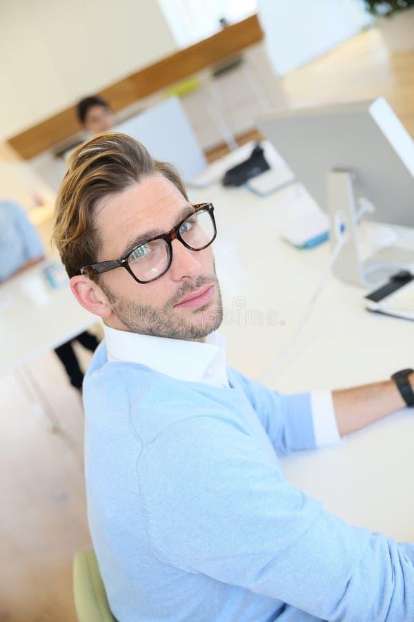 Retrato del hombre de negocios con las lentes en la oficina imagenes de archivo